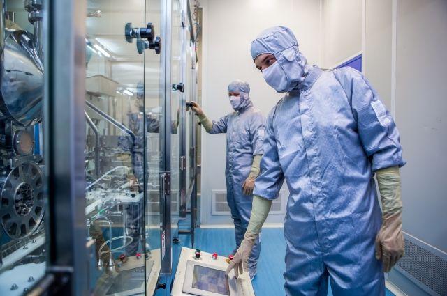 Сотрудник завода выглядит как хирург и трудится на высокотехнологичном оборудовании.