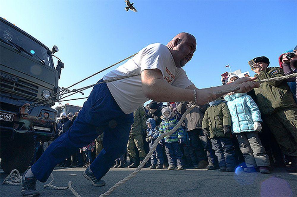 Приморский пауэрлифтер Иван Савкин сдвигает с места армейский грузовик во время праздничных мероприятий в честь Дня защитника отечества во Владивостоке.