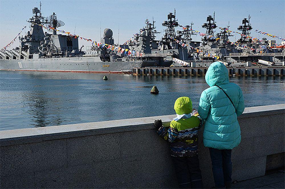 Гвардейский ракетный крейсер «Варяг» (слева) во время празднования Дня защитника Отечества во Владивостоке.