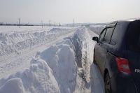 Дорожная служба почистила дорогу, оставив снег между полосами.