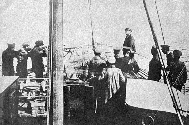 Интервенты расстреливают коммуниста на борту корабля.