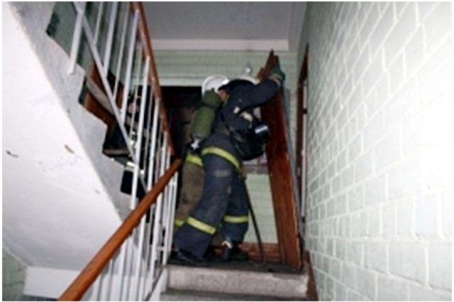 Пожарные зашли в подъезд и поднялись на 3 этаж к квартире, из-под двери которой шел густой черный дым.