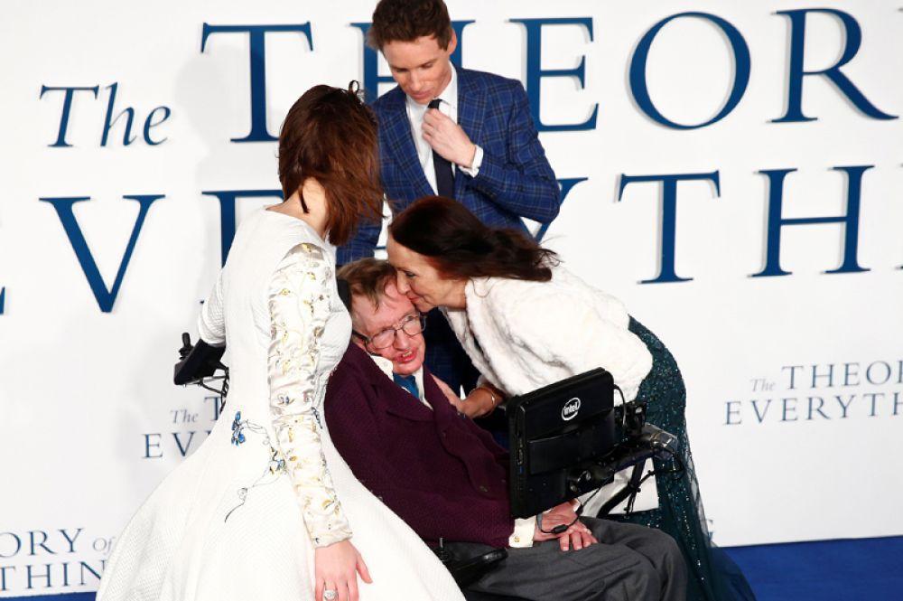 Бывшая жена Стивена Хокинга Джейн Уайлд целует его на премьере фильма «Вселенная Стивена Хокинга» в Лондоне. 9 декабря 2014 года. Рядом — исполнители главных ролей актеры Эдди Редмайн и Фелисити Джонс.