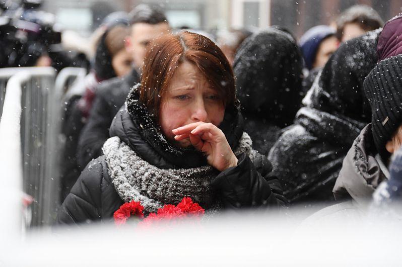 Люди с цветами у входа в здание МХТ имени Чехова.
