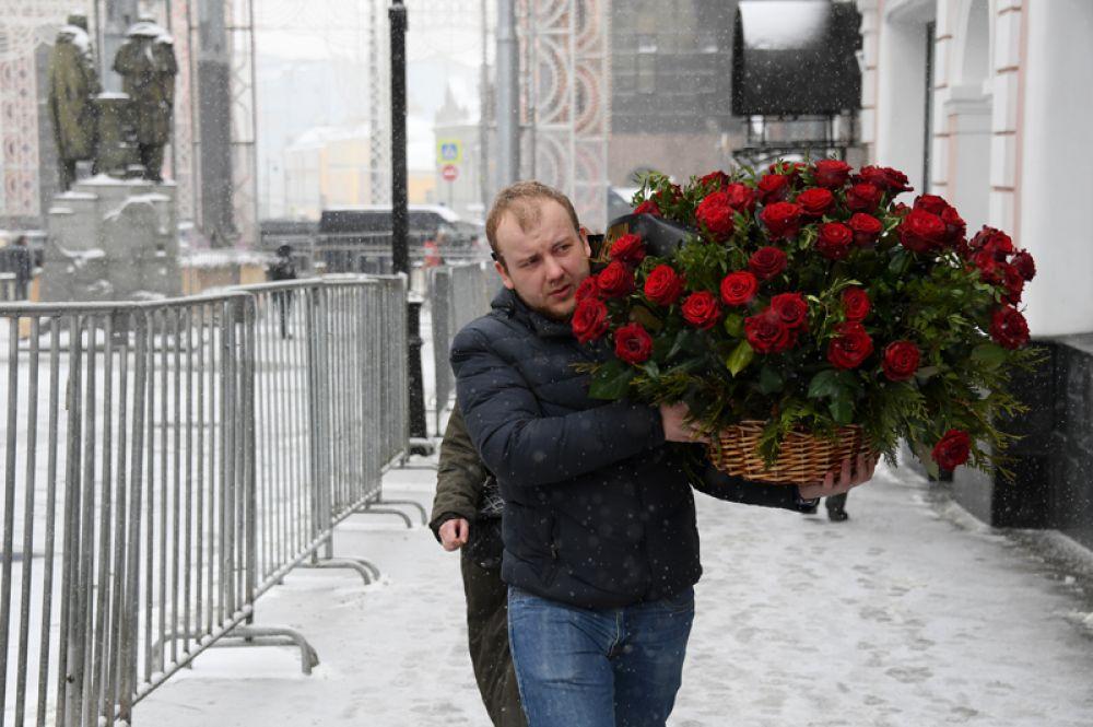 Мужчина несет цветы ко входу в здание МХТ имени Чехова в Камергерском переулке.