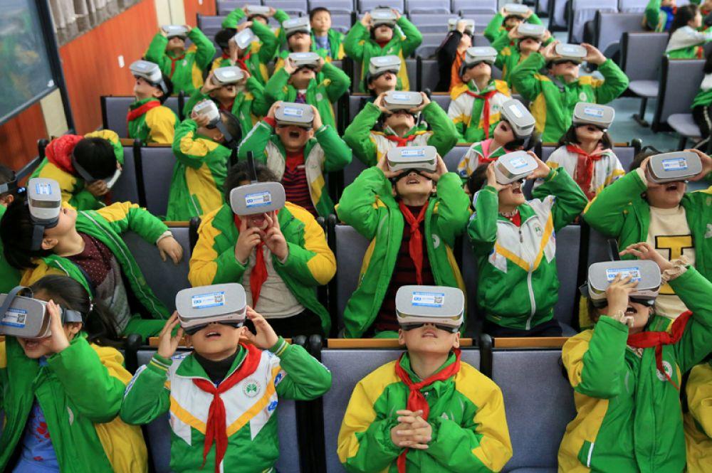 Учащиеся начальной школы в очках виртуальной реальности на уроке, Китай.