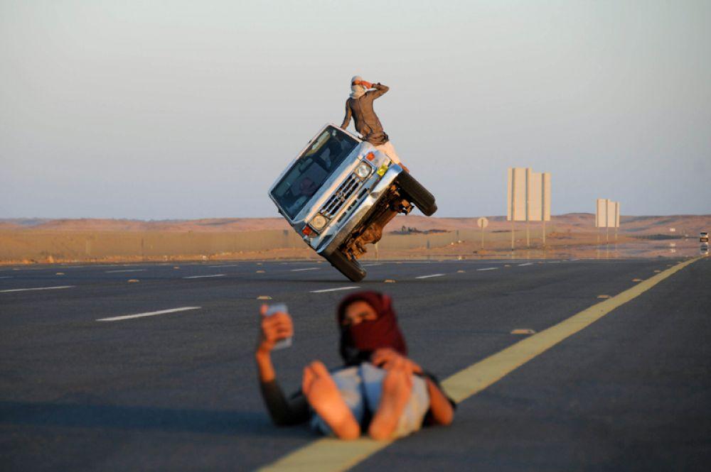 Мужчины выполняют трюк на автомобиле, в то время как юноша делает селфи на их фоне, Табук, Саудовская Аравия.