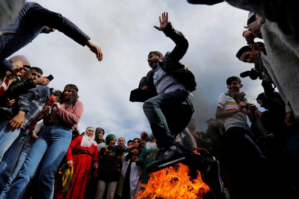 Человек прыгает через костер во время праздника Навруз в Стамбуле, Турция.