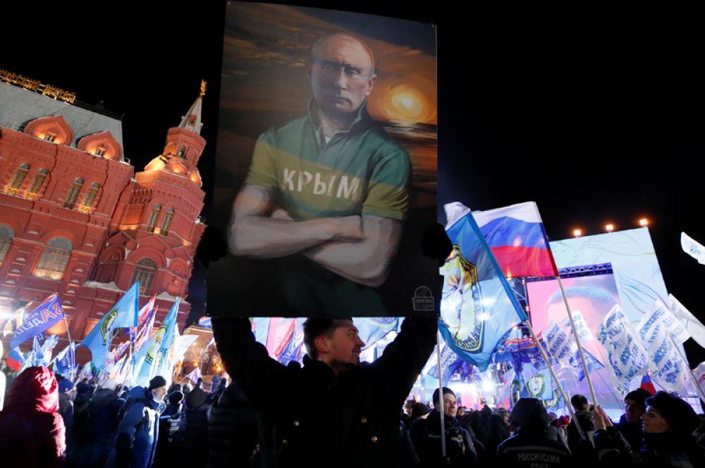 Мужчина держит плакат с изображением Владимира Путина во время концерта, посвященного четвертой годовщине присоединения Крыма к России на Манежной площади, Москва, Россия.