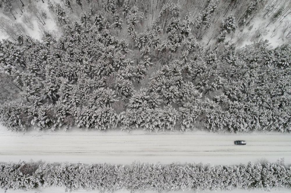 Автомобиль, проезжающий по лесной дороге после снегопада, с высоты птичьего полета, Красноярск, Россия.