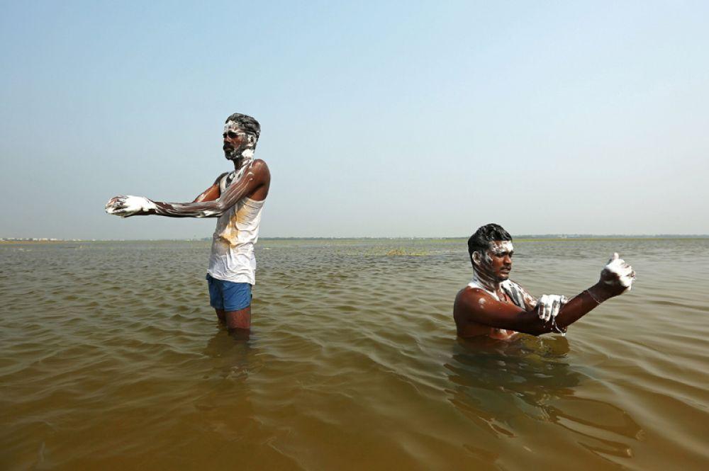 Мужчины купаются в озере по случаю Всемирного дня воды, Ченнаи, Индия.