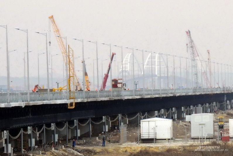 На протяжении всего моста возвышаются строительные краны.