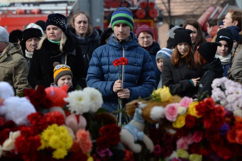 Жители несут цветы и мягкие игрушки к зданию торгового центра «Зимняя вишня» в Кемерово, где произошел пожар.