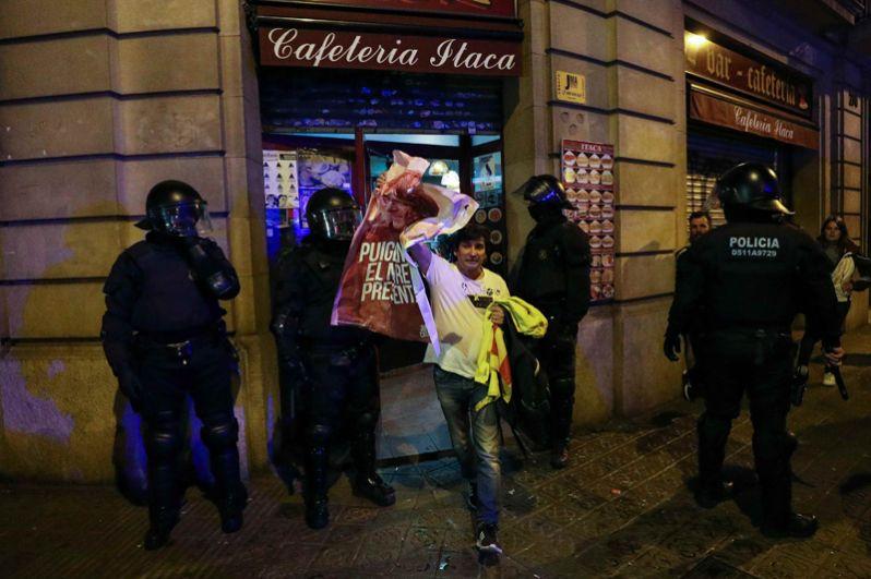 Протестующий во время стычек с полицейскими у одного из кафе Барселоны.