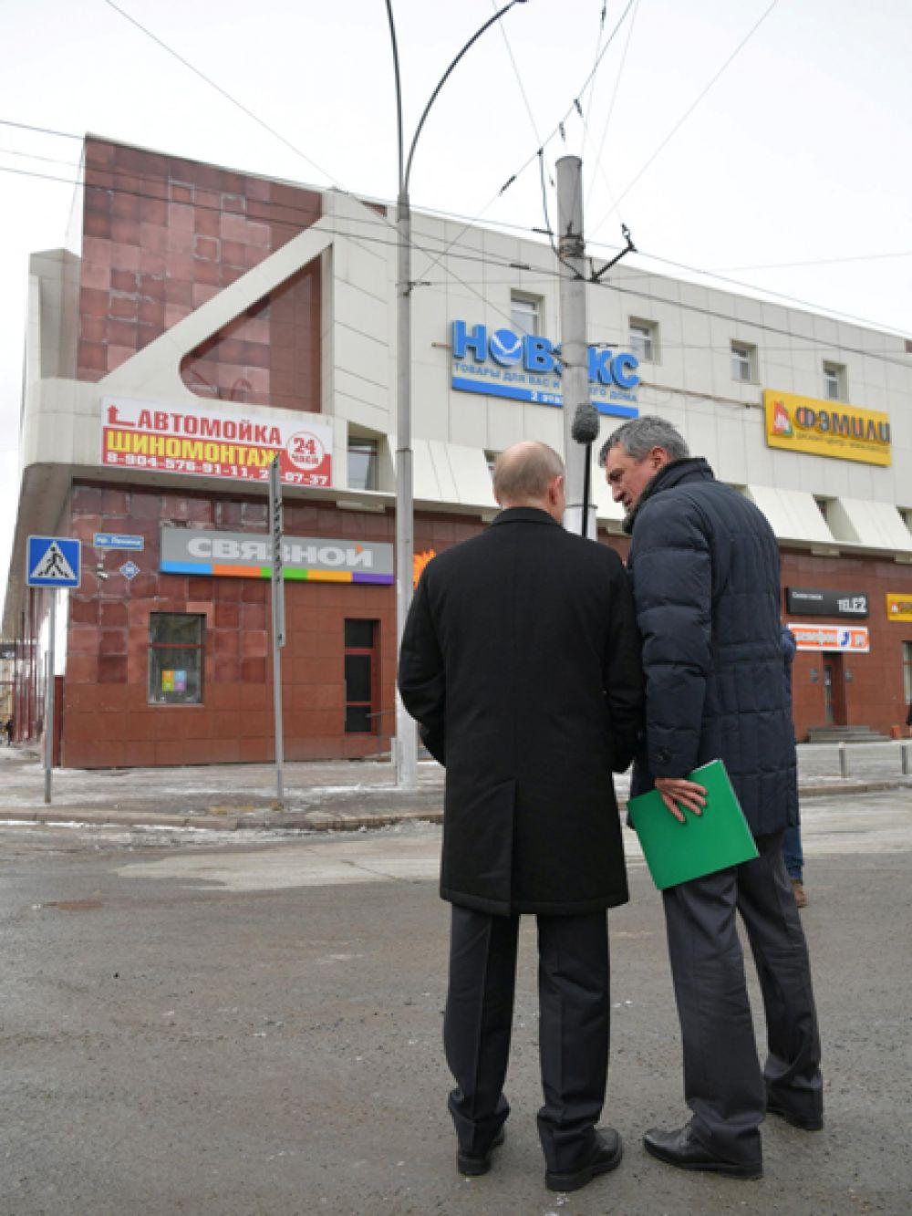 Президент осматривает фасад сгоревшего здания. Его сопровождает полпред президента РФ в Сибирском федеральном округе Сергей Меняйло.