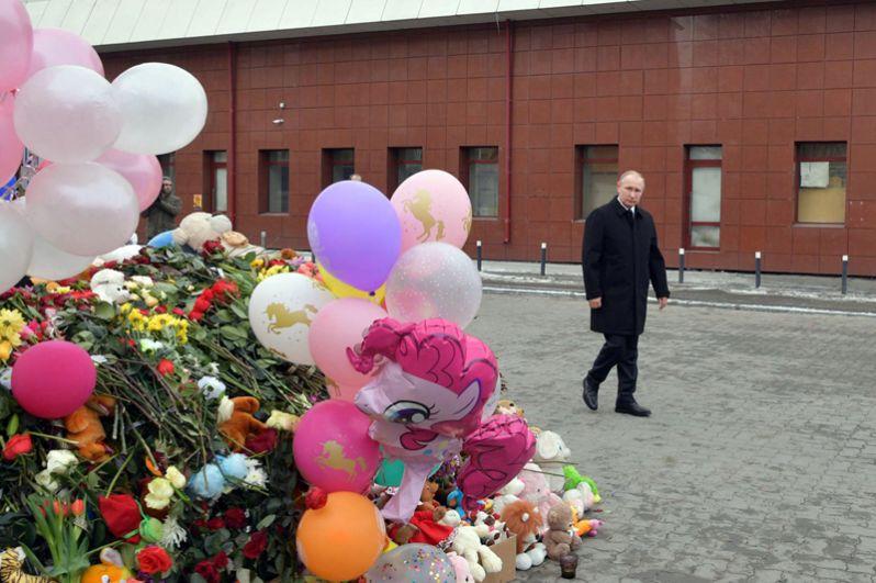 Владимир Путин у стихийного мемориала у фасада сгоревшего ТЦ, куда люди приносят цветы, свечи, игрушки и фотографии погибших.