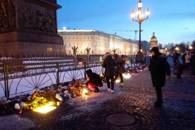 Люди несли цветы к мемориалу на Дворцовой площади.