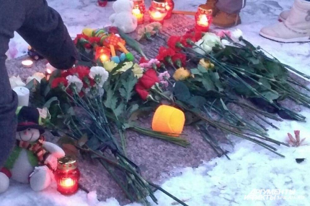 Люди зажигали свечи и возлагали цветы в память о жертвах трагедии в Кемерово.