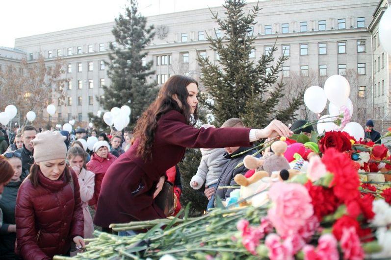 В Иркутске люди несут цветы и свечи.