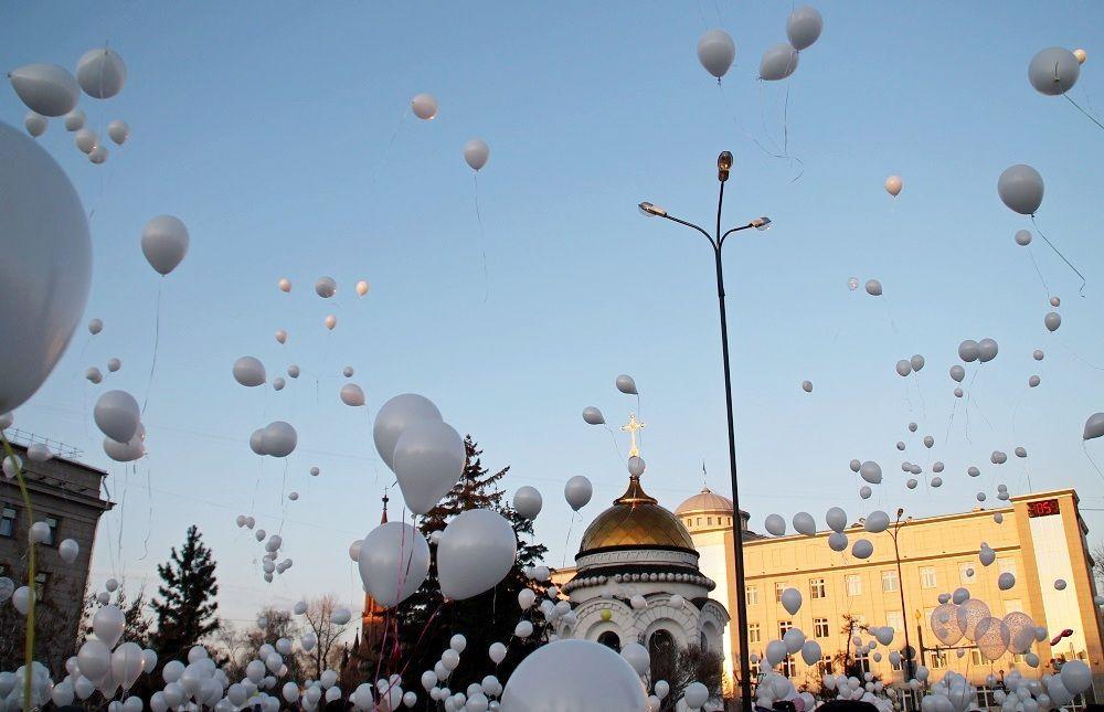 В Иркутске в небо запустили десятки белых шариков в память о погибших детях.