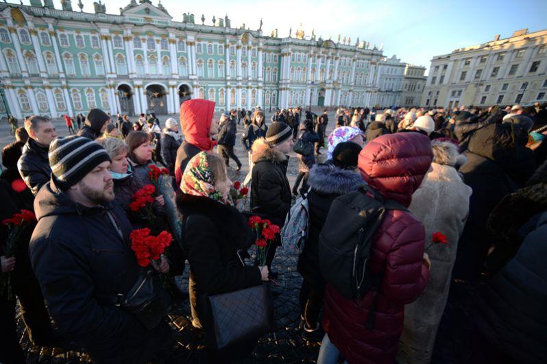 Горожане несут цветы к мемориалу на Дворцовой площади в Санкт-Петербурге.