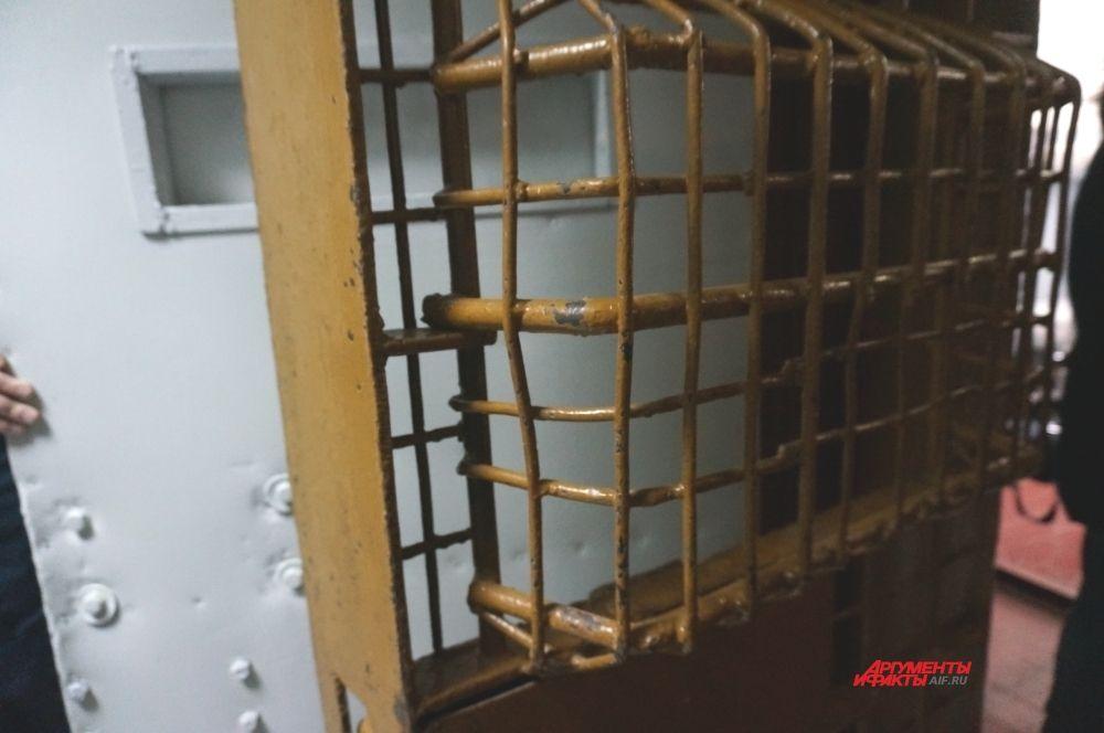 Входную железную дверь из коридора в камеру дублирует другая, из металлических прутьев. В ней есть большое углубление, чтобы дежурный мог заглянуть в камеру не открывая решётчатую дверь.