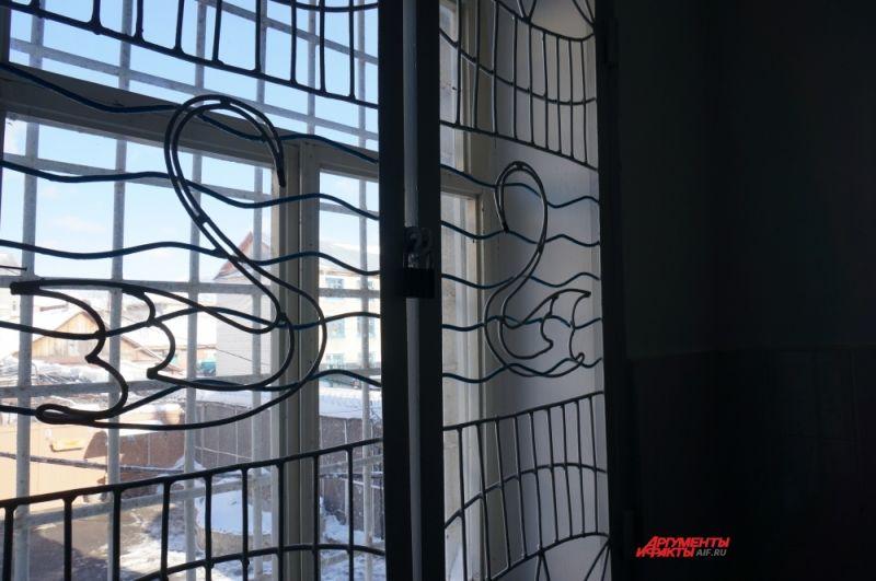 Решётки окон лестничных пролётов в блоке тоже украшены символом колонии.
