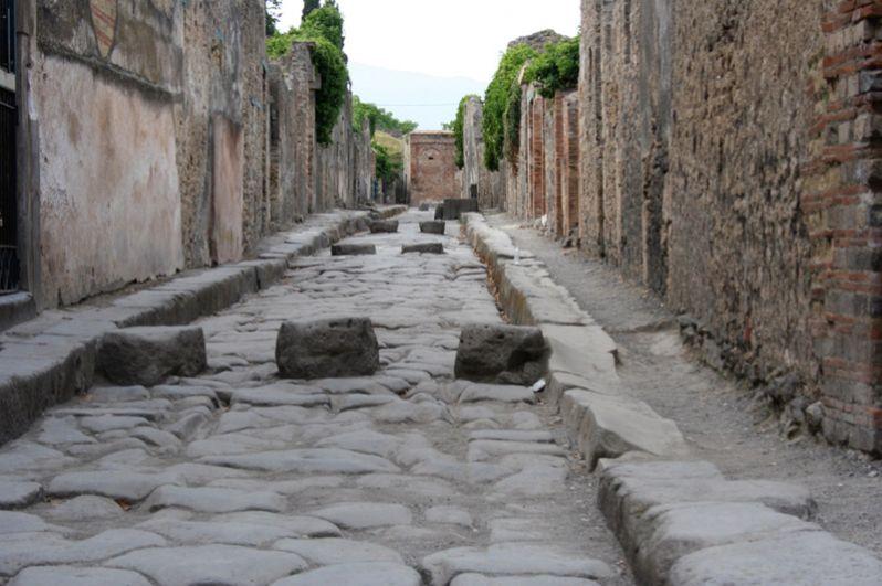 Мощеная улица Помпей. Пешеходы использовали блоки в дороге, чтобы перейти на другую сторону. Промежутки между блоками позволяли транспортным средствам проходить сквозь них.