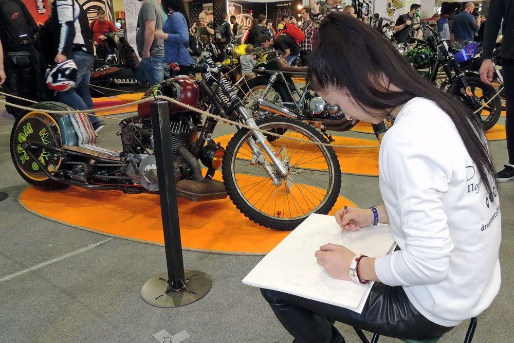 Девушка рисует мотоцикл.