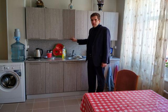 Руководитель центра Денис Бухаров показывает квартиру, обустроенную в приюте.