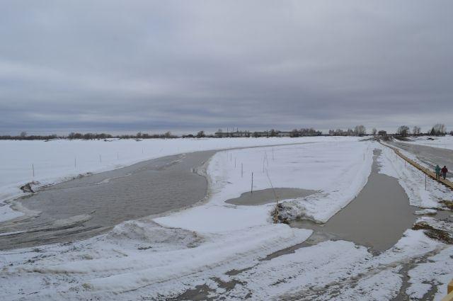 На тающем льду реки Туры стоит будка с собакой