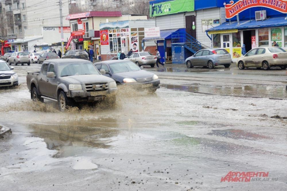 Машины проезжают по дороге, а вода из лужи разливается на несколько метров.