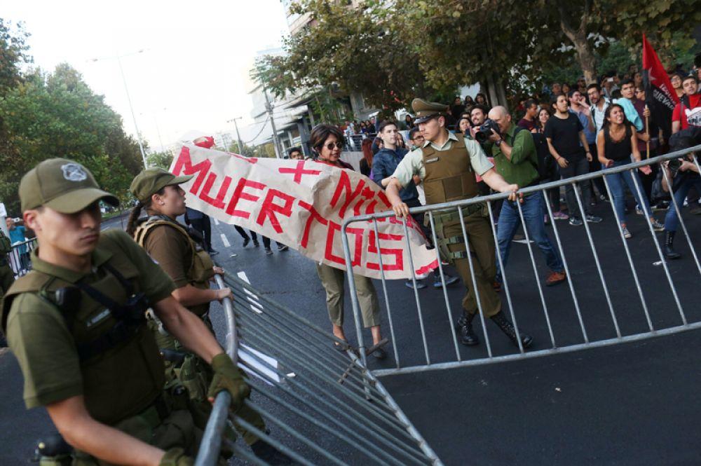 Столкновения участников акции протеста с ОМОН во время митинга около посольства США в Сантьяго, Чили.