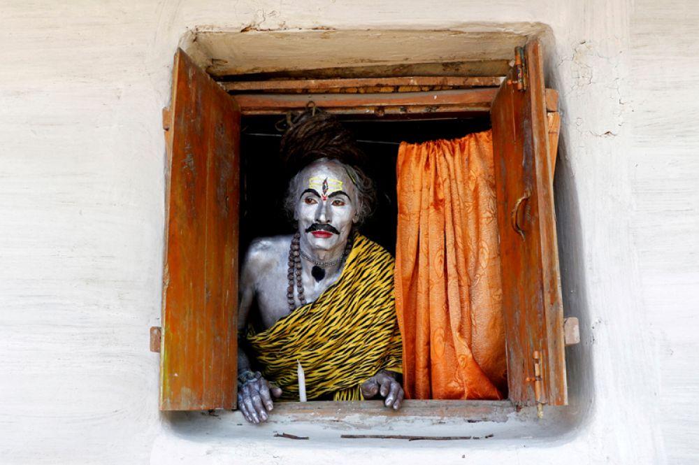 Верующий в костюме бога Шивы в ожидании выступления во время ежегодного религиозного праздника Шива-Гаджан на окраине Агарталы, Индия.