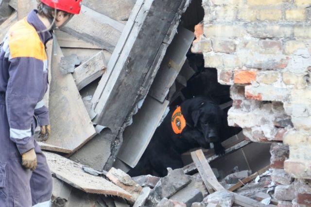 Спасатели помогают людям эвакуировать вещи из руин.