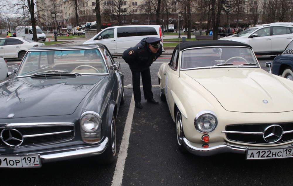 Сотрудник полиции осматривает автомобили участников ралли классических автомобилей.