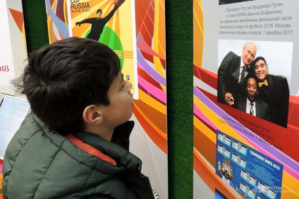 Мальчик смотрит на фотографию Владимира Путина с живыми легендами футбола Марадоной и Пеле.