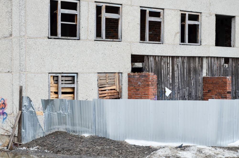 А здание обнесено металлическим забором. Забор успели поставить перед приездом губернатора Свердловской области в 2017 году в рамках его предвыборной кампании.