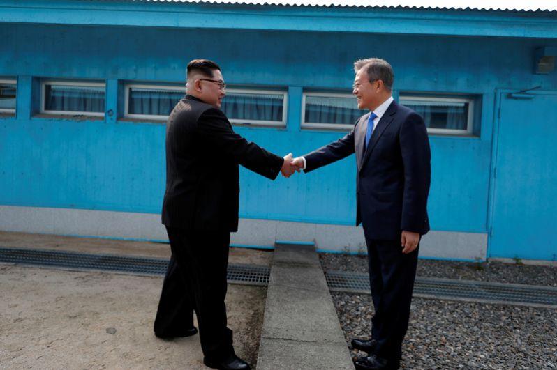 Глава КНДР Ким Чен Ын и президент Южной Кореи Мун Чжэ Ин обменялись рукопожатием при встрече в Пханмунджоме, стоя каждый на своей стороне границы.