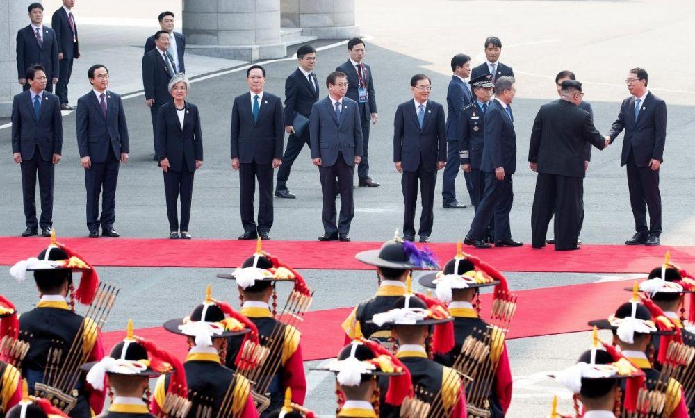 Ким Чен Ын и Мун Чже Ин идут вдоль почетного караула и приветствуют членов делегации.