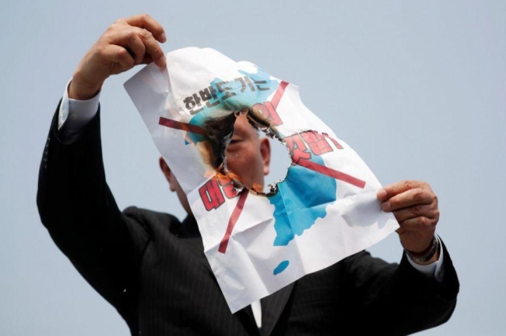 На фото - представитель делегации жжет пропагандистские листовки, призывающие к войне.