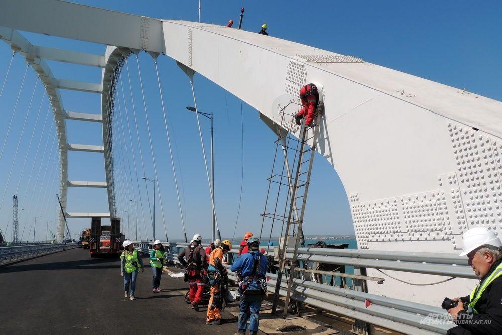 Промышленные альпинисты поднимаются на автомобильную арку моста для монтажа архитектурной подсветки.