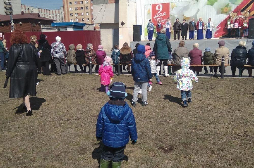 Дети водят хоровод возле сцены.