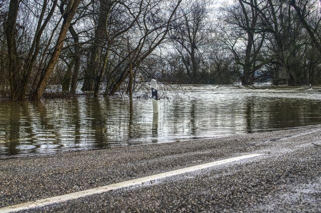 Возле затопленного участка дороги дежурят сотрудники ГИБДД.