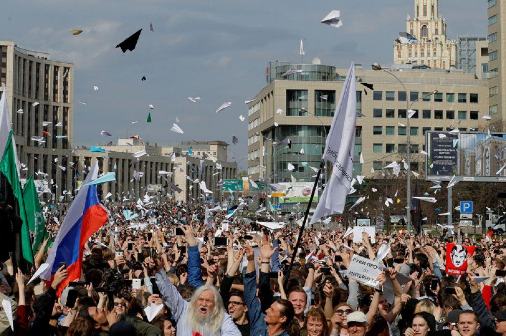 Люди запускают бумажные самолетики во время митинга в знак протеста против решения суда о блокировке Telegram, Москва, Россия.