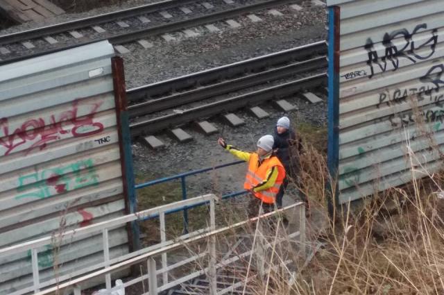 Увидев приближающийся поезд, школьники решили положить найденные здесь же пластиковые бутылки на рельсы.