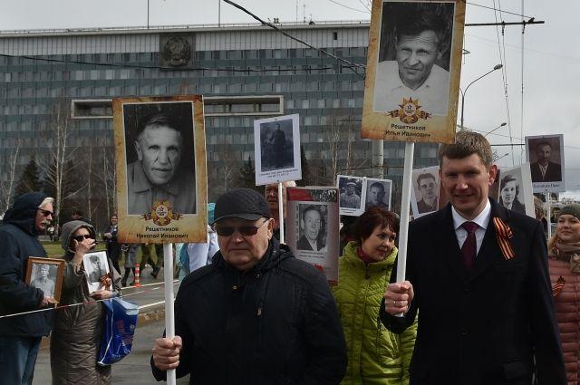 Губернатор и его папа прошли с портретами родных.