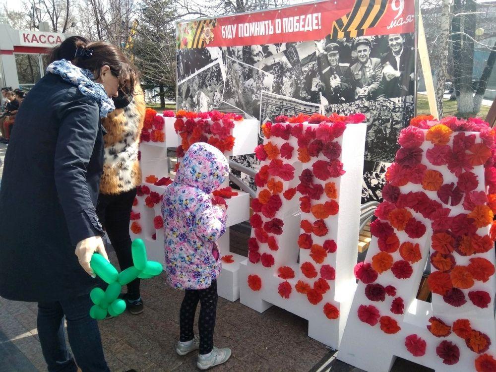 """Дети мастерят цветы и наклеивают их на арт-объект из пенопласта - это слово """"Победа"""""""