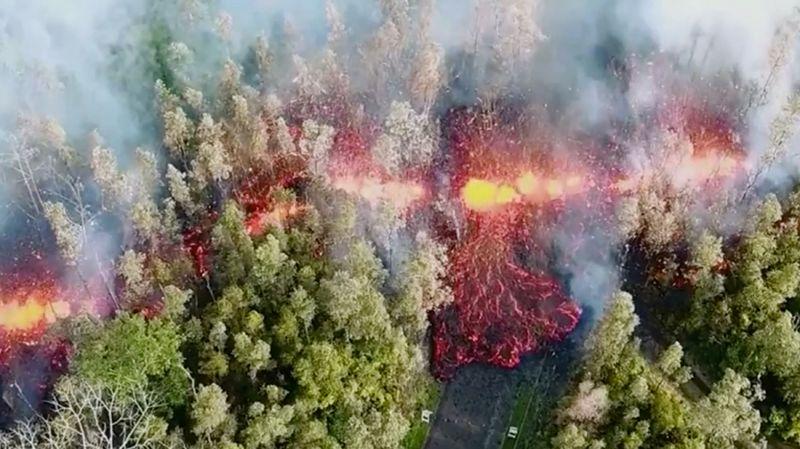 Кадр с беспилотника, показывающий разлом, образовавшийся после извержения. На фотографии видно, как из разлома на поверхность вытекает лава. Рядом с ним стоят дымящиеся деревья, а неподалеку располагаются жилые постройки.