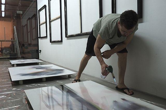 Саша пишет картины, не касаясь их руками: краску направляет движением воздуха, затем покрывает полотно эпоксидной смолой или лаком, сушит.